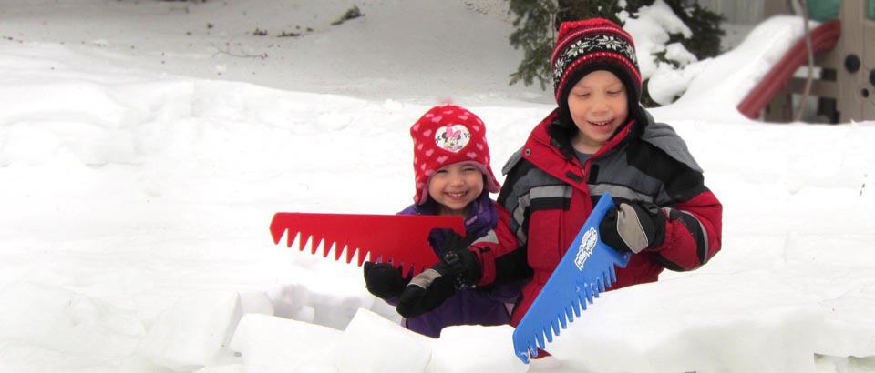 two smiling kids with snowsaws behing a snow fort they made
